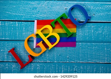Top down image showing LGBTQ spelt in coloured letters on a blue wooden background with a flag