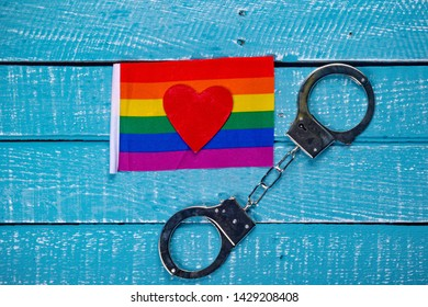 Top down image showing a Pride flag, heart and handcuffs on a blue wooden background