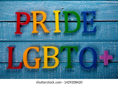 Top down image showing Pride & LGBTQ+ spelt in coloured letters on a blue wooden background
