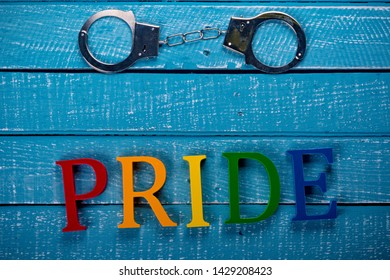 Top down image showing Pride spelt in coloured letters on a blue wooden background with handcuffs
