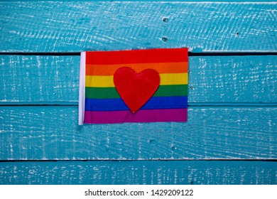 Top down image showing a Pride flag and a heart on a blue wooden background