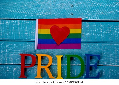 Top down image showing Pride spelt in coloured letters on a blue wooden background with a flag and a heart