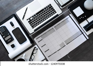 Top down modern office flat lay in a black and white scheme - tablet, smart phone, planner, and coffee