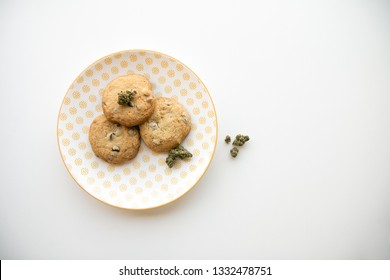 Top Down on Yellow Patterned Plate with Chocolate Chip Cookies and Marijuana Buds