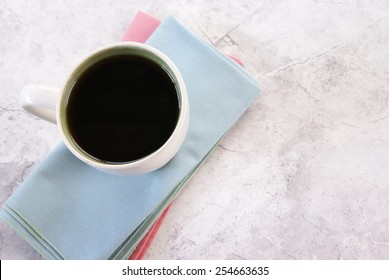 Top down perspective of coffee sitting on two cloth napkins on a marble table.