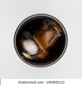 Top - down photo of a glass of cola covered with bubbles. Flat lay soda glass.