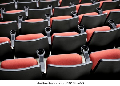 Top down rear view on rows of empty red stadium seats with armrest cupholders, at a stadium or movie theater