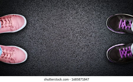 Top down selfie of two pairs of shoes representing two people across each other on asphalt background with copy space. Concept of social distancing during COVID-19 coronavirus outbreak.