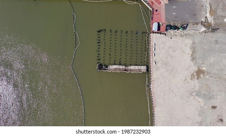 a top down shot directly over a cleared, paved lot next to the Hudson River. In view is an old wooden structure and the remains of many wooden pylons in the river. It is a sunny day.