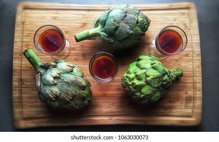 Top down view of 3 cordial glasses of Cynar with artichokes.