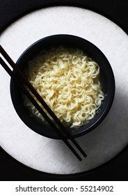 Top down view of asian noodle with chopstick served in a black bowl placed on matching circular background.