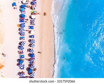 Top down view of a beach with tourists suntbeds and umbrellas with sand beach and clear blue water in Greece