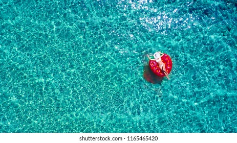 Top down view of a beautiful woman in a white bikini who is floating on a red air mattress