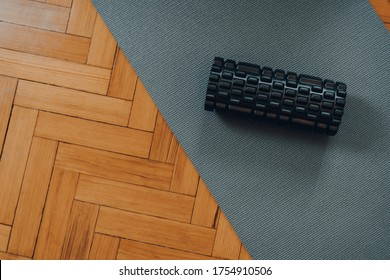 Top down view of a black foam roller on a fitness mat over old parquet floor, selective focus.
