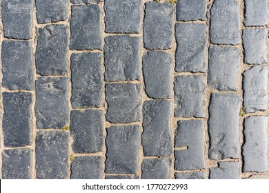 Top down view of black paving stones on Red Square in Moscow, Russia. Small plants grows in some places between the cobblestones. Textured background.