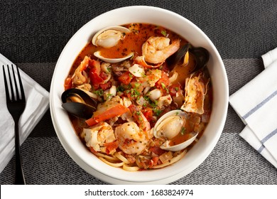 A top down view of a bowl of cioppino, in a restaurant or kitchen setting.
