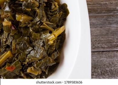 A top down view of a bowl of collard greens, in a restaurant or kitchen setting.