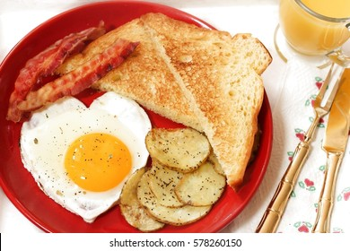 Top down view of Breakfast in bed with egg heart Bacon bread toast roasted potatoes and orange juice served in wooden tray for Valentine's day