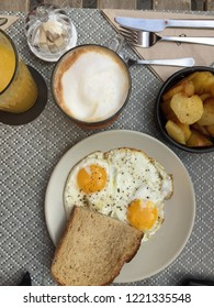Top Down view of Brunch at a French Bistro in Southern France, fried eggs, bread, potatoes, cappuccino, and fresh squeezed orange juice, outside on a sidewalk table