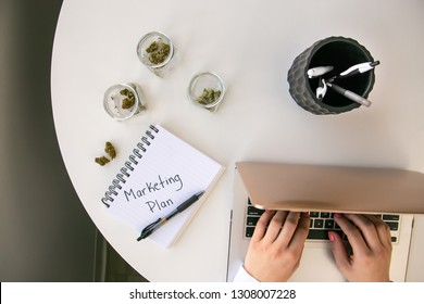 Top Down View of Cannabis Entrepreneur working on Marketing Plan for Marijuana Business on White Table Work Space