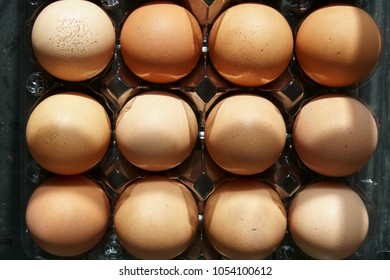Top down view of a carton of brown eggs.