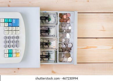 Top down view of cash register full of coins and American paper dollars over wooden table with copy space at side