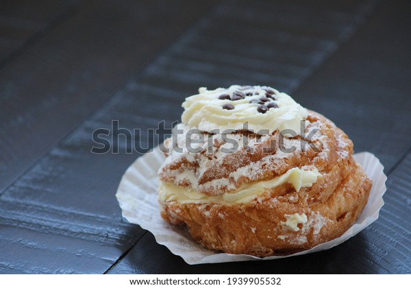 Top down view, close up of one St. Joseph's Day pastry, or Italian Zeppole Di San Guiseppe, with whipped ricotta cheese, chocolate chips, powdered sugar, and fried dough sitting on a sheet of paper.
