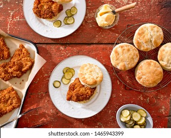 Top down view of Cold Fried Chicken and Biscuits with pickles on red wood table