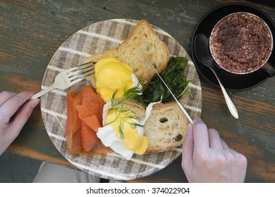 Top down view of eathing healthy breakfast with salmon, egg, bread and spinach