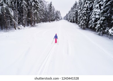 Top down view of the forest in winter. Winter landscape in the forest. Flying over ski track in winter forest. Top down view of ski road. Drone follow the girl skier at ski track. Cross-country skiing