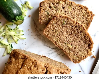 Top down view of freshly baked and sliced zucchini bread on a white granite background