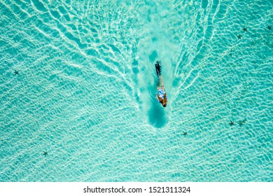 Top down view of a girl swimming in a lagoon. Aerial view of slim woman floating on the water. Summer vacation concept
