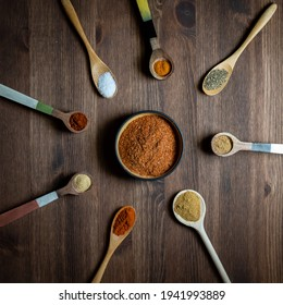 A top down view of a haphazard arrangement of wooden spoons filled with spices used to make a southwest spice blend.