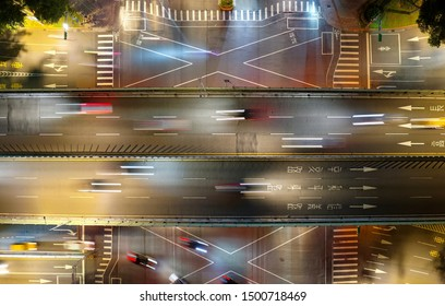 Top down view of Jianguo S. Rd Expressway flying over Ren'ai Road, one of the arterial avenues in Taipei, Taiwan, with light trails of cars dashing on the overpass across the intersection in nighttime