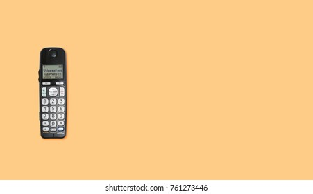 Top down view of old wireless push button phone handset against a yellow background