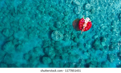 Top down view on a beautiful woman in a white bikini who is floating on a red air mattress