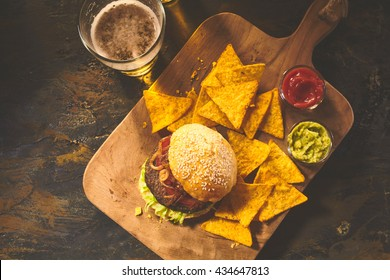 Top down view on burger in sesame bun, tortilla chips, salsa and guacamole on cutting board with beer on table