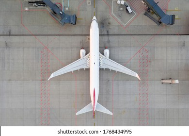 Top down view on comercial airplane docking in terminal in the parking lot of the airport apron, waiting for services maintenance, refilling fuel services after airspace lock down. Modern airliner