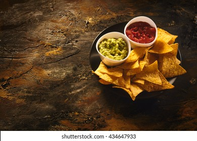 Top down view on delicious crunchy appetizer of triangular yellow corn tortilla chips beside little bowls of guacamole and salsa dip over old dark wooden table with copy space