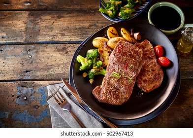 Top down view on delicious meat and potatoes dinner in dark round plate with copy space over wooden table