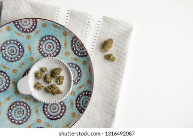 Top Down View on Marijuana Buds on a Vintage Plate atop a Silver Placemat and White Background Minimalist Cannabis