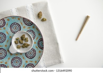 Top Down View on Marijuana Buds on a Vintage Plate and Joint atop a Silver Placemat and White Background Minimalist Cannabis