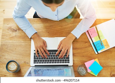 Top down view on pair of female hands of woman typing on laptop computer with coffee and office supplies next to it