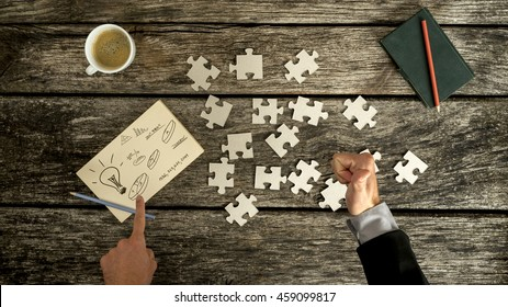 Top down view on thumb up and finger pointing to business symbols on notecard beside blank jigsaw puzzle pieces, checkbook and cup over old wooden table.