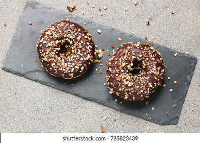 Top down view on two donut with cocolate and chopped almonds lying on slate stone serving plate