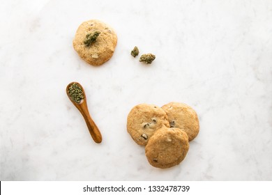 Top Down View on White Marble of Edible Marijuana Chocolate Chip Cookies, Cannabis Buds and Ground Weed on a Wooden Spoon