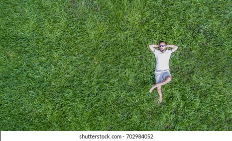 Top down view on a young man wearing sun glasses and lying on a vivid juicy green grass relaxing in a hot summer day