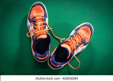 Top down view of orange and white badminton sport shoes on the green floor