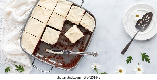 Top down view of a pan of red velvet chocolate brownies topped with cream cheese frosting, ready for serving.