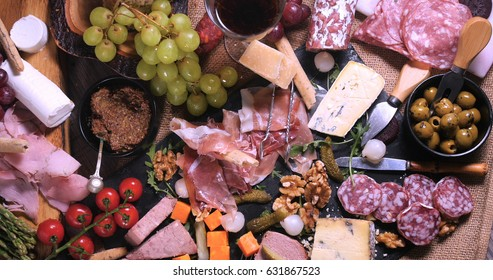 Top down view of a platter of cured meat (charcuterie), ham, salami, pate and cheese
